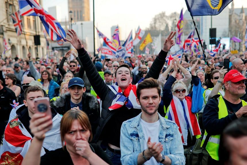Pro-Brexit protesters gesture and wave flags outside the Houses of Parliament in London, March 29, 2019.