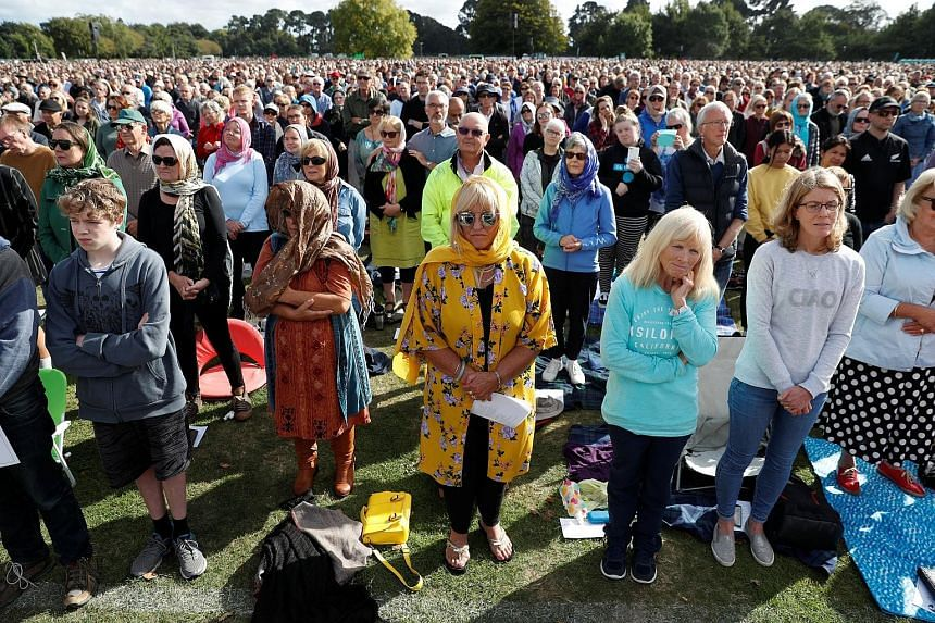 People, including some women wearing headscarves, attending the memorial service at Hagley Park in Christchurch.