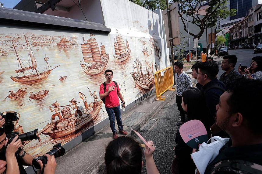 Mr Yip Yew Chong, who painted a 44m-long mural behind the Thian Hock Keng Temple depicting the life of early Hokkien immigrants when they first arrived in Amoy Street, introducing the artwork to participants of the preview of the Singapore Maritime Trail