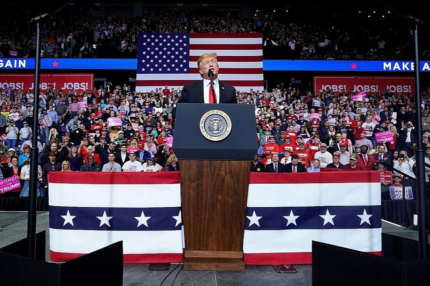 """President Donald Trump speaking at a campaign rally in Grand Rapids, Michigan, on Thursday. He called his opponents """"losers"""" and celebrated the fact that the special counsel's investigation has ended."""
