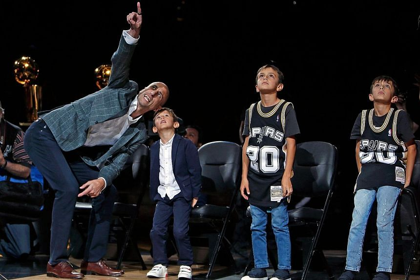 Retired NBA player Manu Ginobili with his children as his No. 20 jersey was hoisted to the rafters at AT&T Centre on Thursday in San Antonio, Texas.