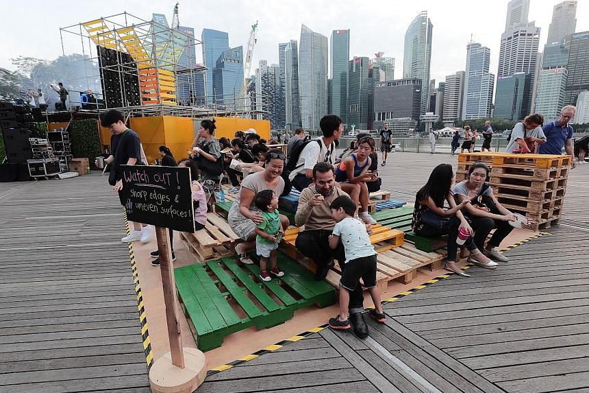 Mr Sameer Grover and his wife Lisa Teo, both 38, enjoying family time with their children Nathaniel, three, and Ethan, one, on recycled wooden pallets at the Earth Hour 2019 festival yesterday.