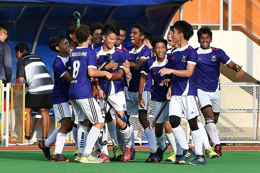 The St Andrew's Secondary hockey team celebrate winning the Schools National B Division final at the Sengkang Hockey Stadium yesterday. The Saints beat Victoria School 1-0.