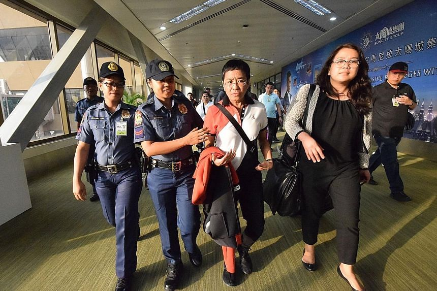 Philippine journalist Maria Ressa (centre) being escorted from Manila's international airport yesterday after being served with an arrest warrant.