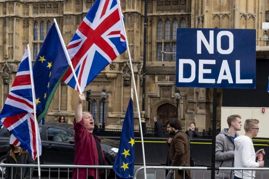 Anti-Brexit activists display the Union and EU flags as they demonstrate outside the Houses of Parliament in Westminster, London on March 28, 2019.