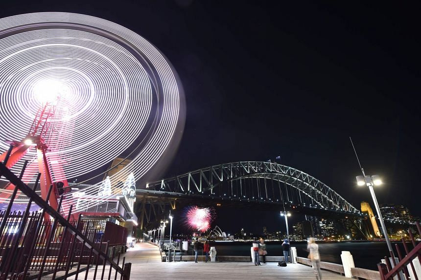 The Sydney Harbour Bridge, the Opera House and the ferris wheel are seen before being plunged into darkness.