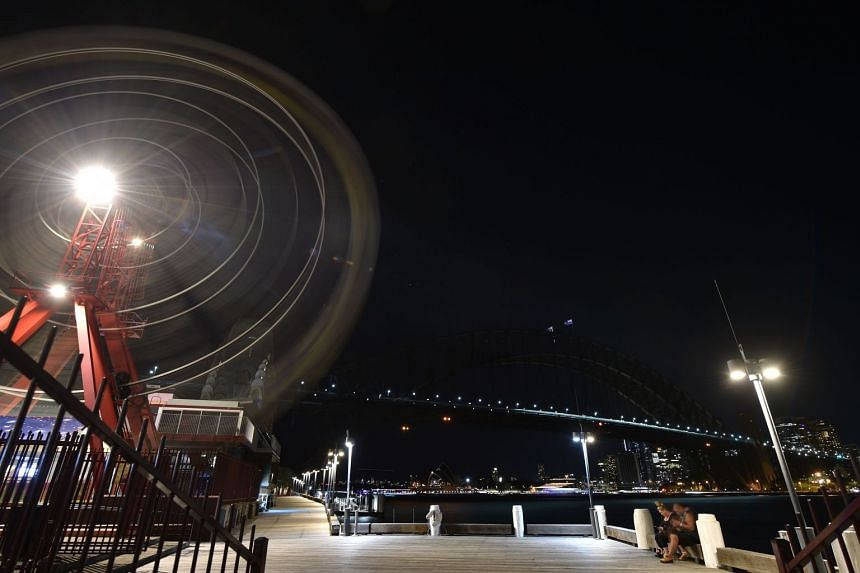 The Sydney Harbour Bridge, the Opera House and the ferris wheel are seen after their lights went out.