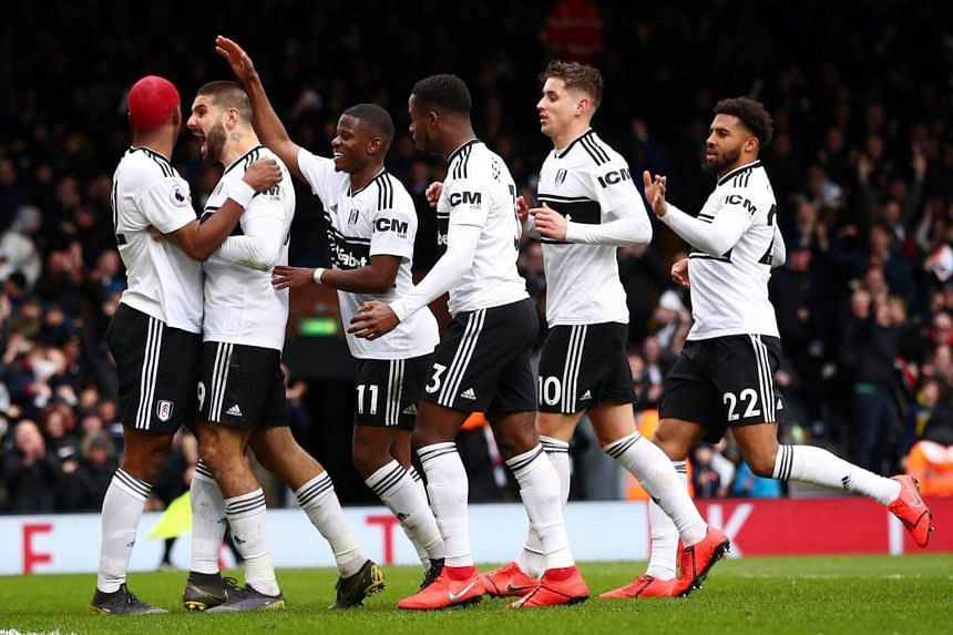 Fulham players celebrate after scoring a goal against Liverpool at Craven Cottage in London, on March 17, 2019.