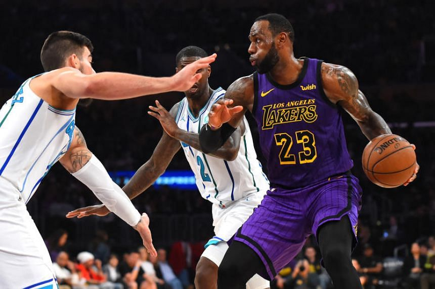 Charlotte Hornets' Willy Hernangomez (left) and forward Marvin Williams (centre) guard Los Angeles Lakers' LeBron James (right) as he drives to the basket in the second half of the game at Staples Center on March 29, 2019.