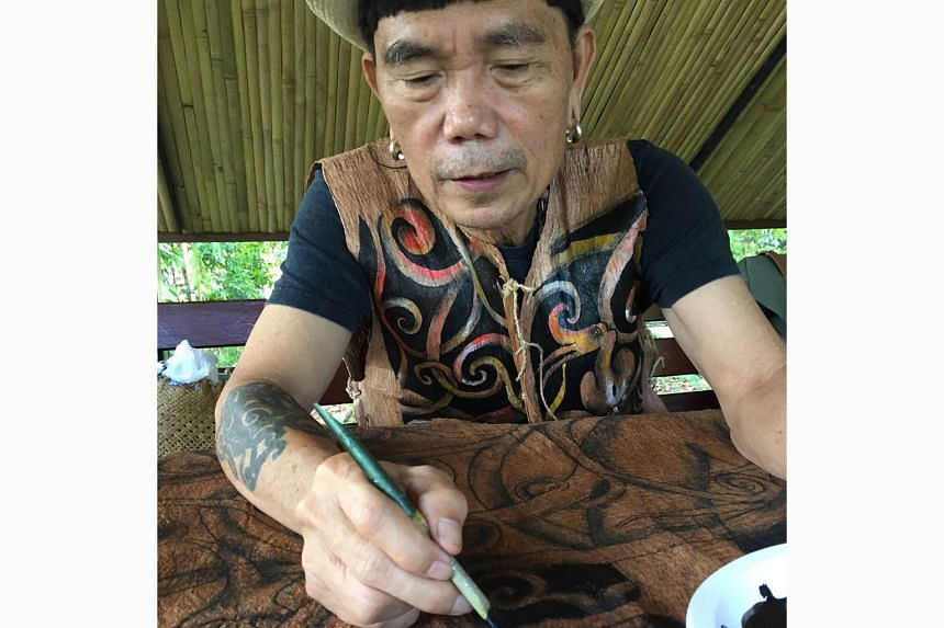Above: The bamboo pavilion with walls that make music at the Rainforest Fringe Festival in Kuching last June. Left: Artist Matthew Ngau Jau painting the Tree Of Life at the Singapore Botanic Gardens last June.