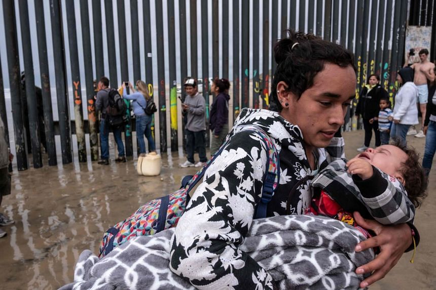 A Central American migrant carries a child after being sprayed by Border Patrol agents while trying to cross the US-Mexico border fence from Tijuana to San Diego on March 21, 2019.
