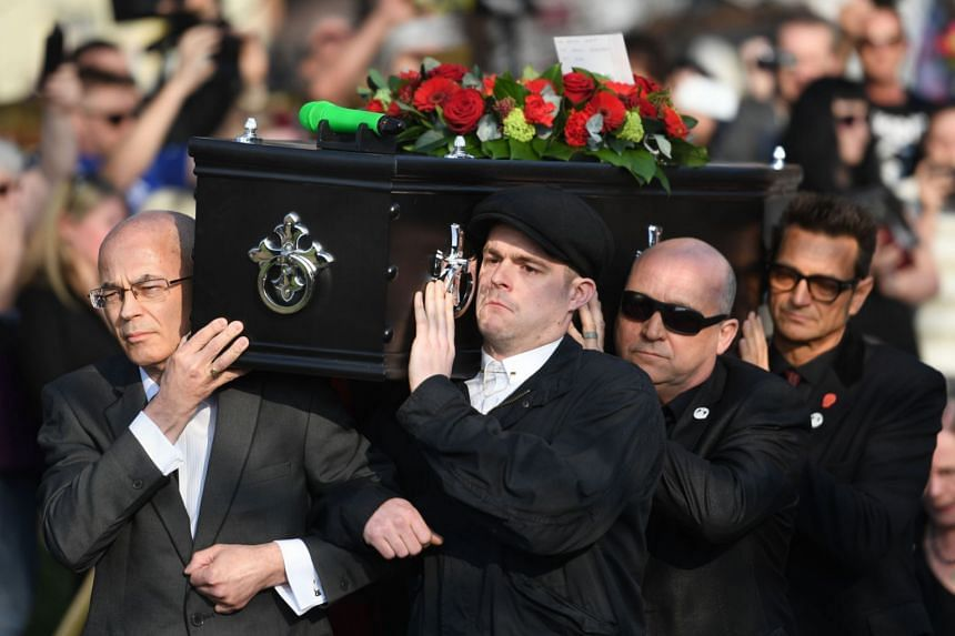 Flint's coffin is carried into St Mary's Church ahead of his funeral.