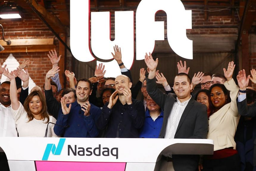 Lyft CEO Logan Green (centre) and president John Zimmer (centre, left) applaud during the Nasdaq opening bell ceremony celebrating the company's IPO.