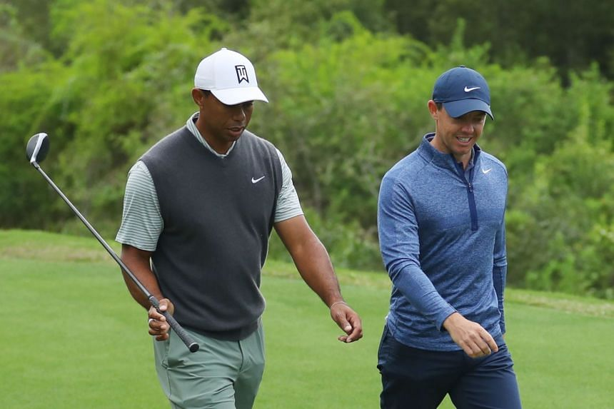 Woods (left) and McIlroy walk on the third hole during the fourth round.