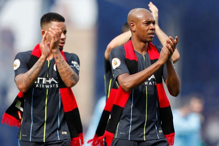 Manchester City's Fernandinho and Gabriel Jesus applaud fans after the match.
