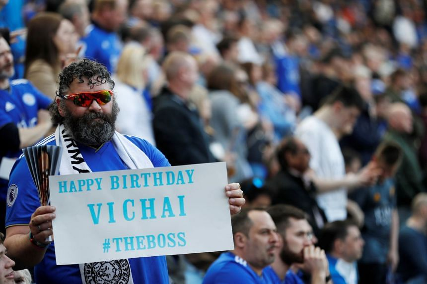 A fan holds up a banner in reference to Leicester City's late chairman before the match.
