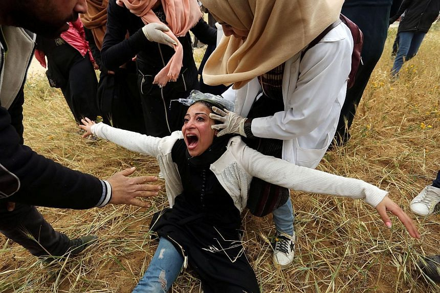 """A Palestinian woman reacting after inhaling tear gas during clashes with Israeli forces yesterday, following a demonstration marking the first anniversary of the """"Great March of Return"""" protests, near the border with Israel east of Gaza City."""