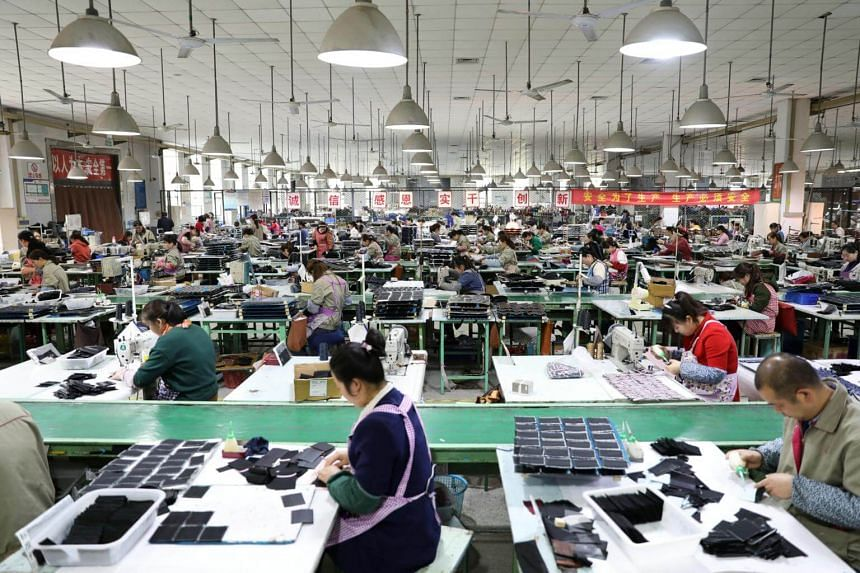 Employees work on the production line of a factory manufacturing fashion accessories in Sihong county, Jiangsu province, China, on March 27, 2019.