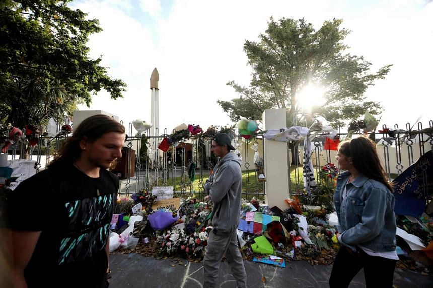 People walk past flowers and tributes displayed in memory of the twin mosque massacre victims outside the Al Noor mosque in Christchurch, on March 29, 2019.