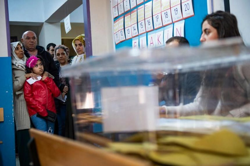 People queue to vote at a polling station during local elections in Istanbul on March 31, 2019.