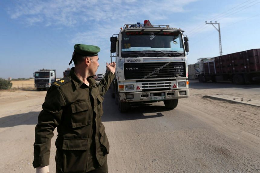 A member of the Palestinian Authority security forces waves forth a truck carrying goods at the Kerem Shalom border crossing in the southern Gaza Strip, on Nov 7, 2017.