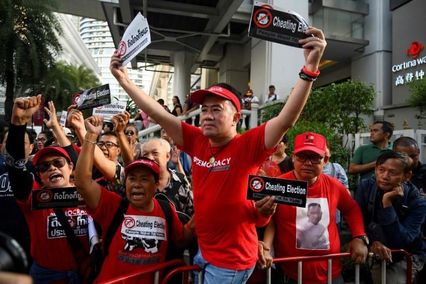 """A small but spirited group gathered near the tourist hotspot Erawan Shrine holding a banner that read """"Cheating Election"""" and """"People Want to Vote""""."""