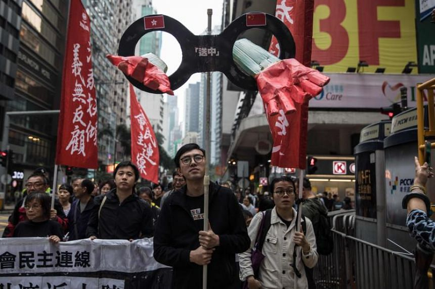 Protesters march along a street during a rally in Hong Kong on March 31, 2019 to protest against the government's plans to approve extraditions with mainland China, Taiwan and Macau.