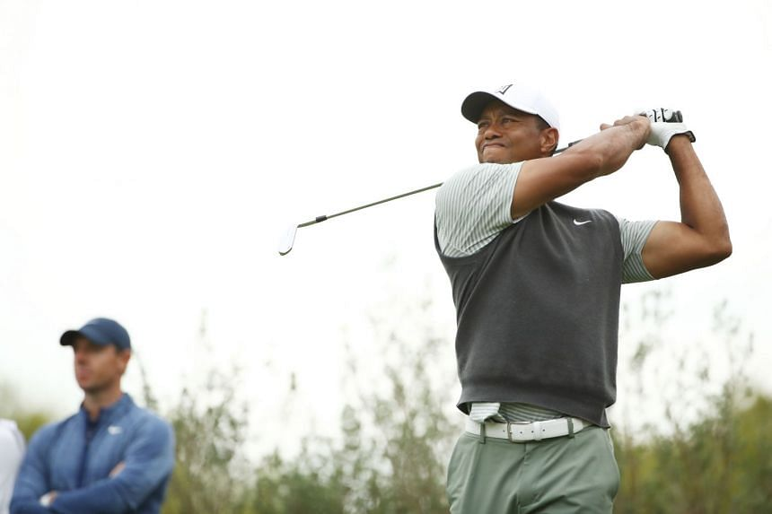 Woods plays his shot from the 11th tee as McIlroy looks on during the fourth round.