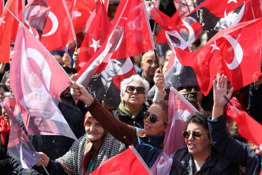 Supporters of the main opposition Republican People's Party mayoral candidate Ekrem Imamoglu wave Turkish flags and portraits of Mustafa Kemal Ataturk, founder of secular Turkey, during a rally for the upcoming local elections in Istanbul, Turkey, Ma
