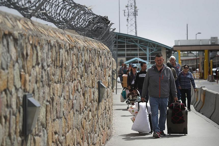 People walking into the United States from Mexico over the Paso del Norte International Bridge in El Paso, Texas.