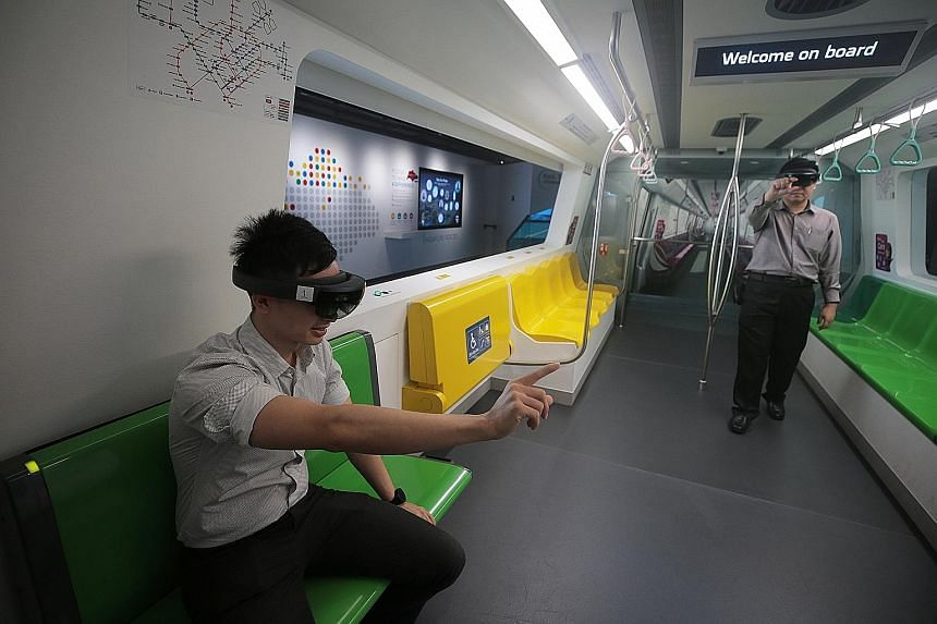 LTA project engineer Edmund Lee (left) and senior project engineer Liu Jiahan demonstrate using augmented reality glasses inside a replica MRT train cabin at the Singapore Mobility Gallery.