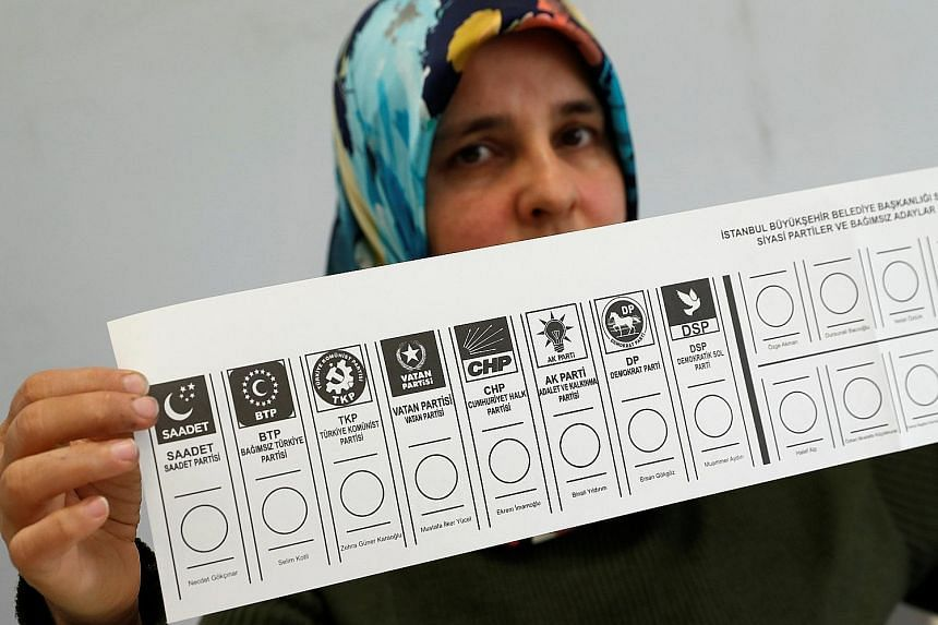 An election official holding up a ballot card at a polling station in Istanbul. Yesterday's elections were the first since Turkish President Recep Tayyip Erdogan assumed sweeping presidential powers last year.