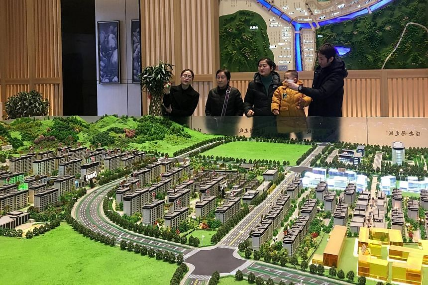 A sales agent in Shaanxi province, China, giving a sales pitch at a real estate showroom. For more than a decade, China has been considering a nationwide property tax but it has not happened due to resistance from property developers and owners, and