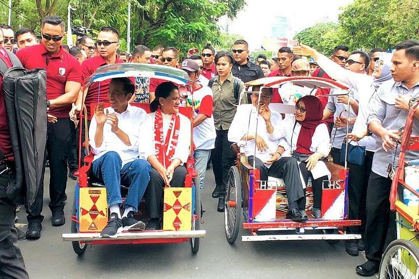 Incumbent President Joko Widodo and his wife Iriana (left) in a becak while campaigning in Makassar in South Sulawesi yesterday. Outgoing Vice-President Jusuf Kalla and his wife Mufidah are in the other pedicab.