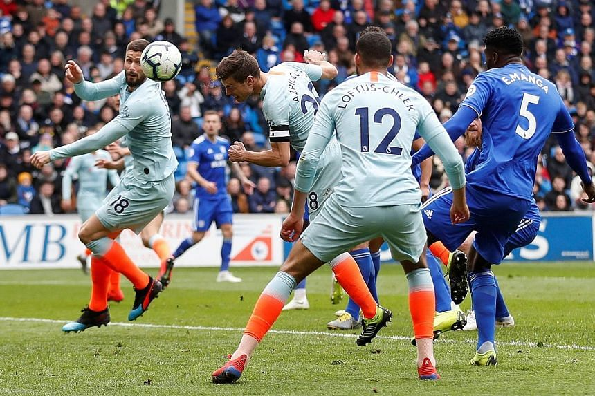 Left: Chelsea substitute Ruben Loftus-Cheek celebrating scoring the last-gasp winner with teammate Olivier Giroud in the 2-1 win against Cardiff City yesterday. Below: Cesar Azpilicueta heading in the equaliser for Chelsea but replays showed he was c