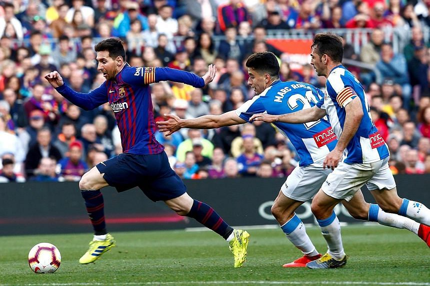 Barcelona's Lionel Messi racing past Espanyol's Marc Roca and skipper Victor Sanchez during the Spanish LaLiga match on Saturday. The Argentina ace scored both goals to take his tally to 41 in all competitions this season - the 10th straight year he