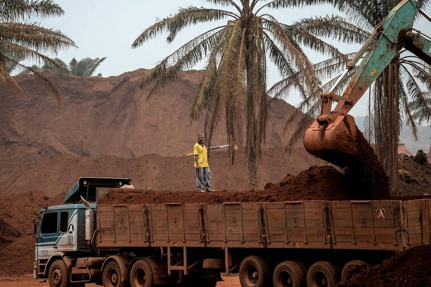 A truck driver watches as an excavator loads his vehicle at a bauxite storage site in Pahang, Malaysia.