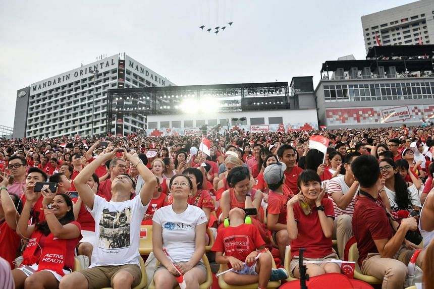 """Spectators at the National Day Parade. Mr K. Shanmugam said Singapore's racial and religious harmony """"didn't fall ready-made from the sky"""" but was engineered over many decades, and that multiracial meritocracy was not unassailable."""