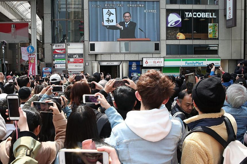 "Pedestrians take pictures of a television programme showing Chief Cabinet Secretary Yoshihide Suga announcing the new era name ""Reiwa"" in Osaka on April 1, 2019."