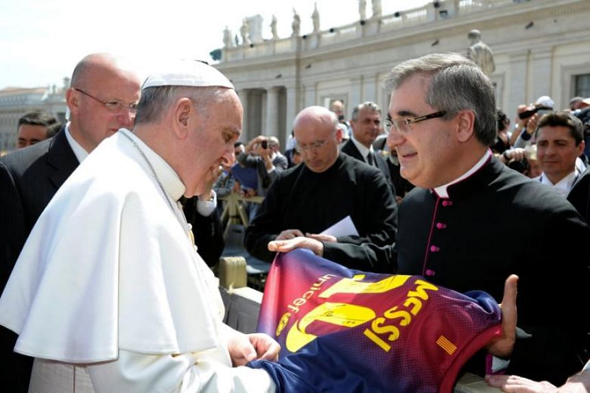 Pope Francis receives a Barcelona soccer jersey of player Lionel Messi during the weekly audience in Saint Peter's Square at the Vatican in 2013.