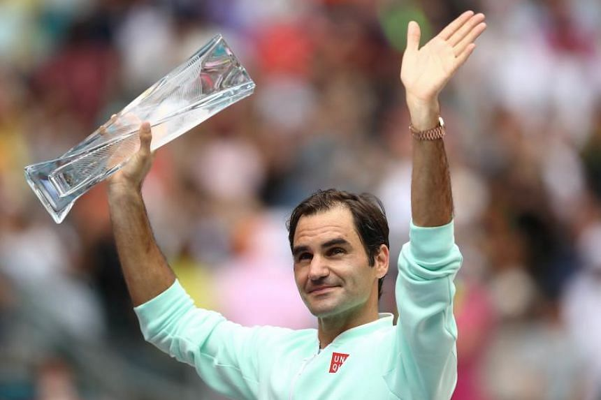 Roger Federer of Switzerland celebrates with the winners' trophy against John Isner of US (not pictured) in the final during day 14 of the Miami Open tennis on March 31, 2019 in Miami Gardens, Florida.