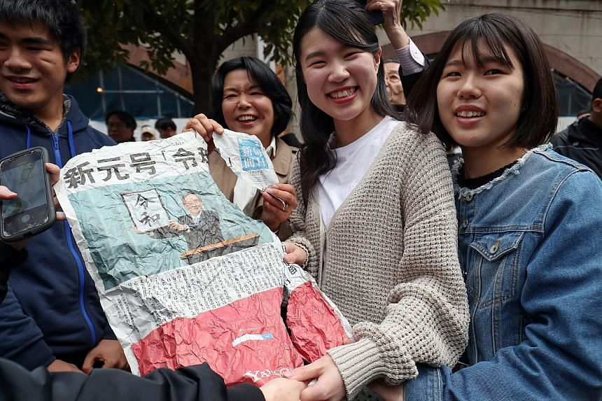 Women posing with a newspaper page showing the unveiling of the name of the new era after a scramble to secure a copy in Tokyo yesterday.