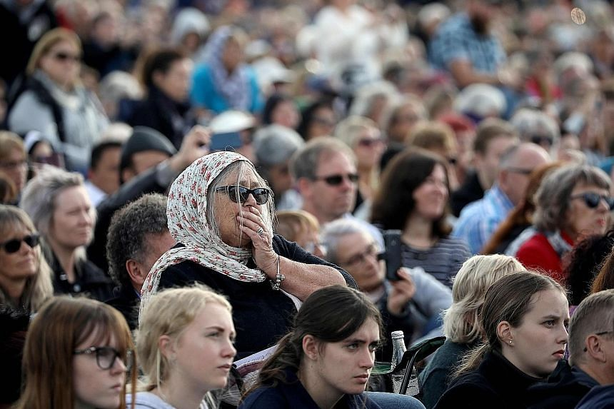 Attendees at a remembrance service at Christchurch's North Hagley Park last Friday for the victims of the March 15 shootings. A week after the attacks, New Zealand proposed new laws to ban military-style semi-automatic weapons. PHOTO: AGENCE FRANCE-P