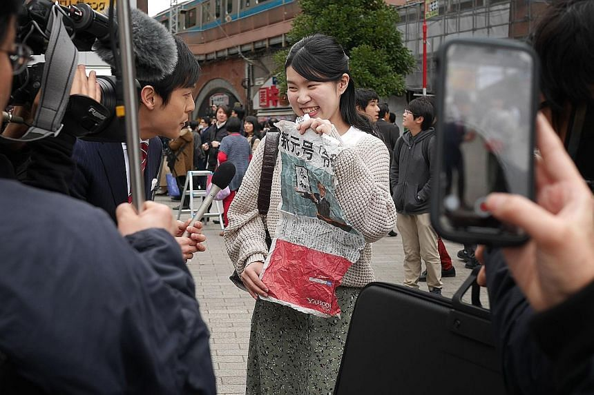 A TV crew interviewing a woman who managed to obtain a newspaper's extra edition reporting the announcement of the new era's name. The Oak Door's head chef Patrick Shimada, with the 3kg whopper to commemorate the coronation of Crown Prince Naruhito o
