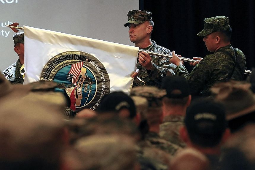 US exercise director, Brigadier-General Chris McPhillips (centre), unfurling a flag of the 35th Balikatan exercise between the Philippines and the US during the opening ceremony in Manila yesterday. The war games are being held to enhance interoperab