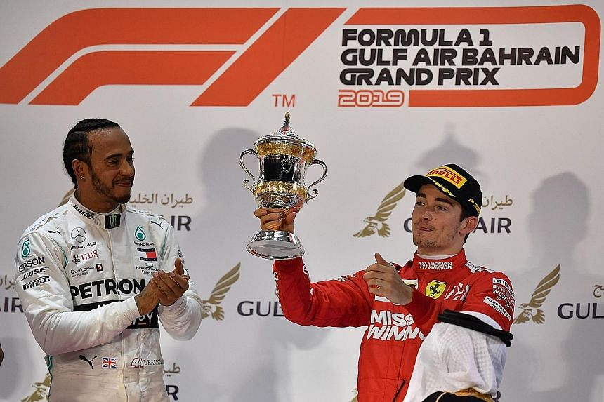 A heartbroken Charles Leclerc with his third-place trophy as winner Lewis Hamilton leads the cheers at the Sakhir circuit.