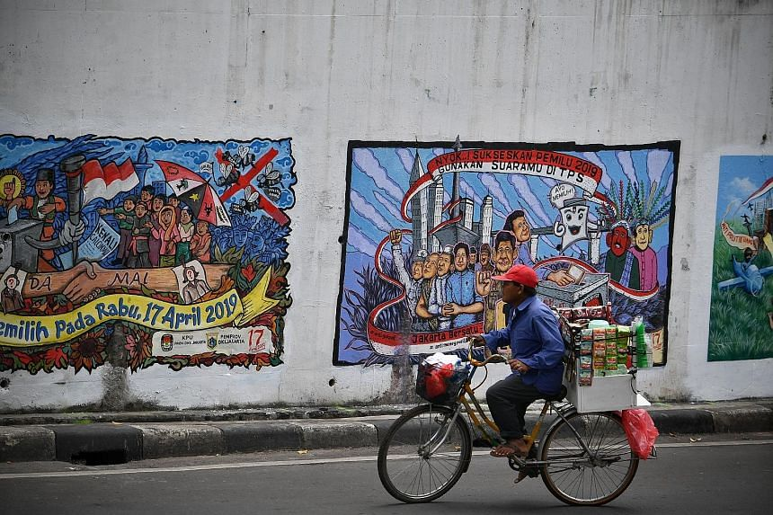 A vendor cycling past political murals on a wall in Central Jakarta yesterday. The Prabowo-Sandiaga team claims there are irregularities in the final voter list which could lead to electoral fraud if not resolved.