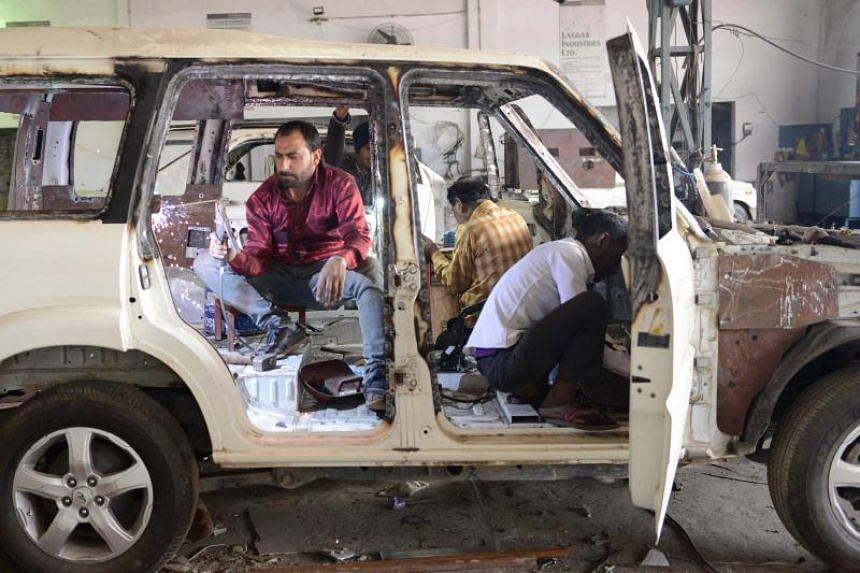 Indian mechanics work to bulletproof a vehicle at the Laggar Industries workshop on the outskirts of Jalandhar.