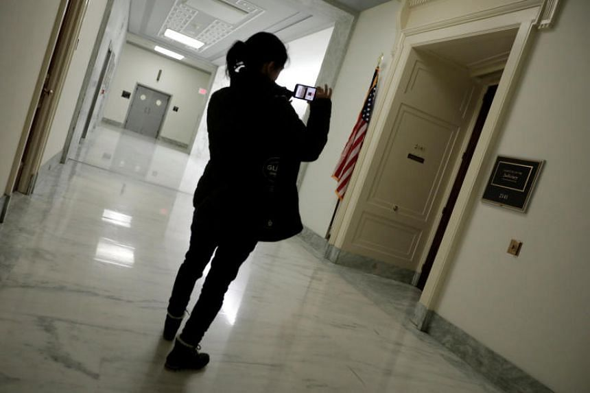 A reporter takes pictures of the US House Judiciary Committee office in Washington, DC, on March 22, 2019. An increasing number of student journalists want to do more than report on problems - they want to solve them, students and faculty say.