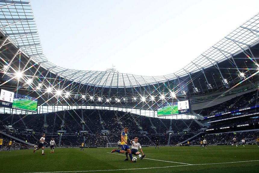 Top: Fans stream into the new Tottenham Hotspur stadium to watch Spurs legends play their Inter Milan counterparts. Above: The stadium had earlier hosted Tottenham's U-18 Premier League match against Southampton, during which Spurs' J'Neil Bennett ha